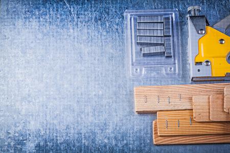 staple gun: Construction stapler chrome staples wood building board on metallic background. Stock Photo