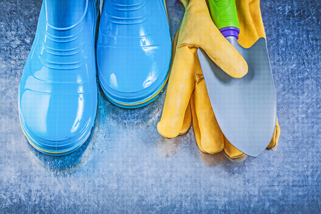 working gloves: Safety gum boots working gloves hand trowel on metallic background gardening concept. Stock Photo