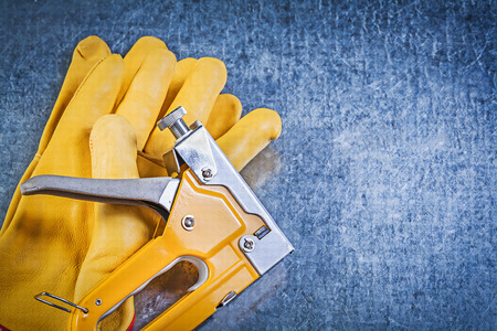 staple: Composition of leather safety gloves staple gun on metallic background construction concept. Stock Photo