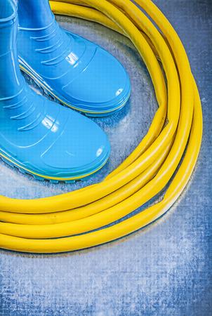 gum boots: Safety gum boots rubber garden hose on metallic background gardening concept.