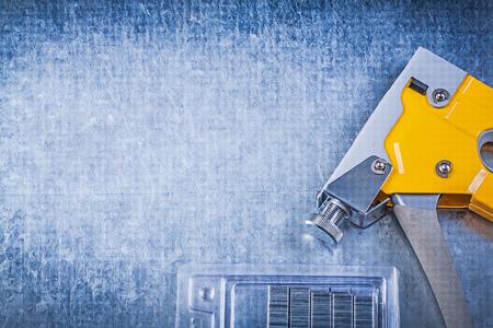 staple gun: Yellow tacker stapler gun chrome staples on scratched metallic background.