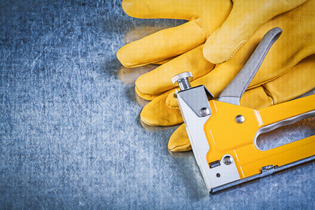 staple gun: Pair of safety gloves staple gun on metallic background construction concept.