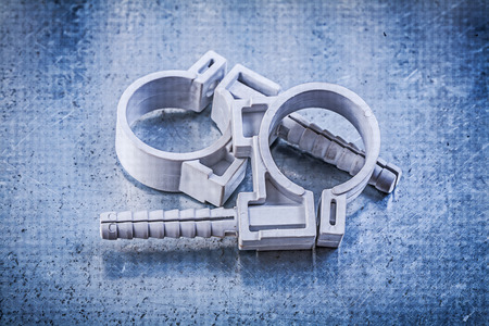 stainless steel range: Pvc pipe clamps on metallic background construction concept.