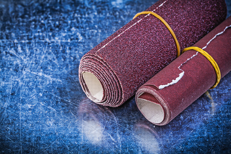 emery paper: Rolls of emery paper on metallic background abrasive equipment. Stock Photo