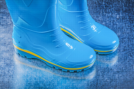 gum boots: Pair of safety rubber boots on metallic background gardening concept.