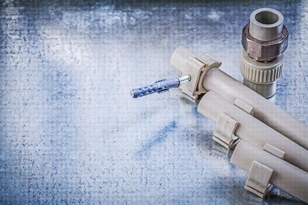 fixtures: Plastic water pipe fixtures connectors on metallic background construction concept. Stock Photo