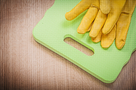 protective: Protective gloves kneeling pad on wooden board gardening concept.