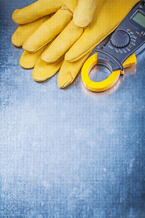 electricity background: Digital clamp meter safety gloves on metallic background electricity concept.
