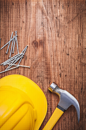 hard hat: Claw hammer metal construction nails hard hat on wooden board. Stock Photo