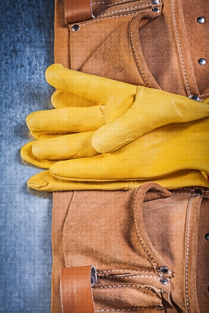 toolbelt: Pair of safety working gloves toolbelt on metallic background construction concept. Stock Photo