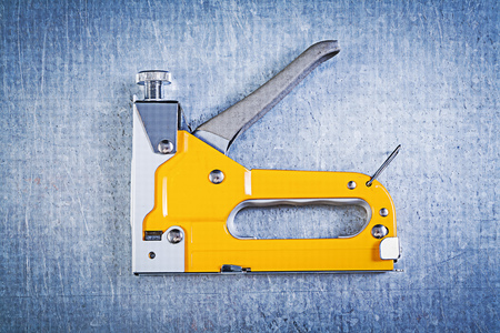 staple gun: Construction stapler on metallic background top view.