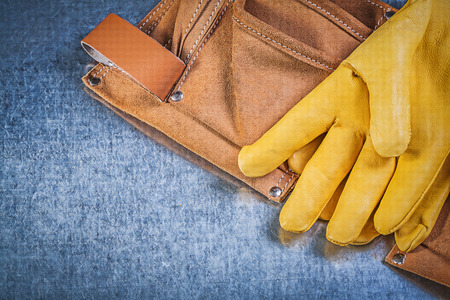 toolbelt: Yellow leather protective gloves tool belt on metallic background construction concept.
