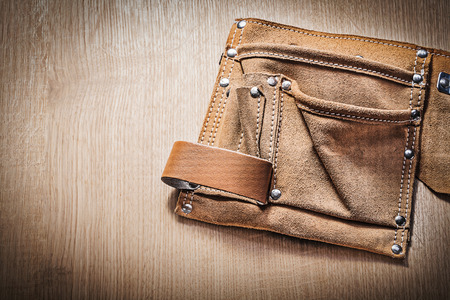 tool belt: Leather tool belt for building tooling on wooden board.
