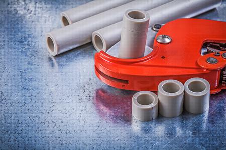 kunststoff rohr: PVC-Wasserrohrschneider auf metallischen Hintergrund Ansicht von oben Baukonzept. Lizenzfreie Bilder