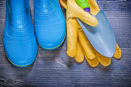 gum boots: Leather safety gloves metal hand spade waterproof rubber boots on wooden board agriculture concept. Stock Photo