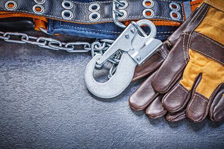 cinturon seguridad: Guantes de la construcci�n del cintur�n de seguridad en el fondo negro concepto de mantenimiento.
