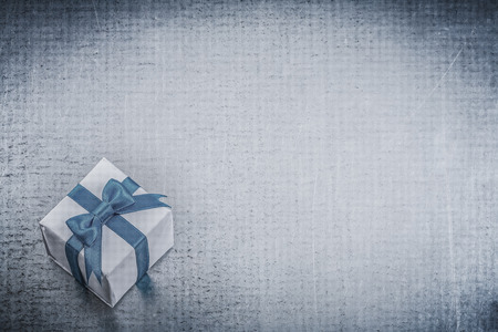 giftbox: Giftbox with tied blue bow on metallic background holidays concept. Stock Photo