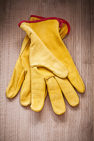 working gloves: Close up image of leather working gloves on wooden board gardening concept.