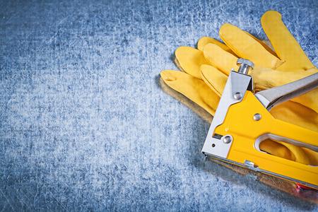 staple gun: Set of safety gloves stapler gun on metallic background construction concept. Stock Photo
