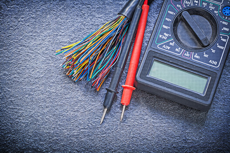 the tester: Digital multimeter electrical tester cables on black background electricity concept.
