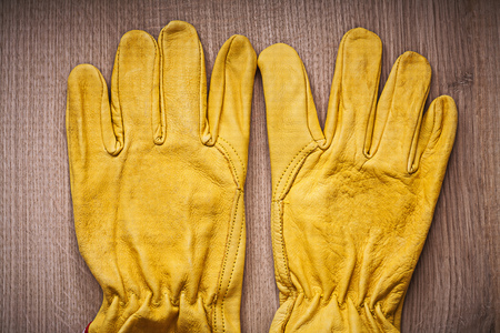 gardening gloves: Pair of yellow leather protective gardening gloves on wooden board agricultural concept. Stock Photo