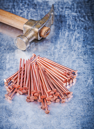 construction nails: Vintage claw hammer heap of copper construction nails on scratched metallic background. Stock Photo