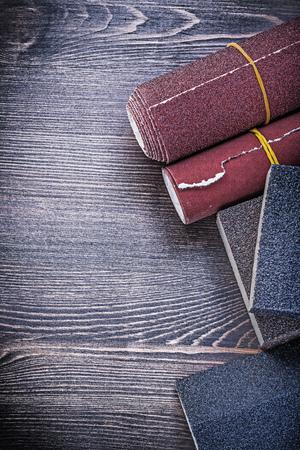 emery paper: Rough abrasive paper sponges on vintage wood board construction concept.