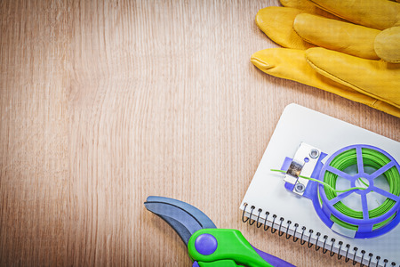 pruning shears: Safety gloves pruning shears garden tie wire checked notepad on wood board gardening concept.