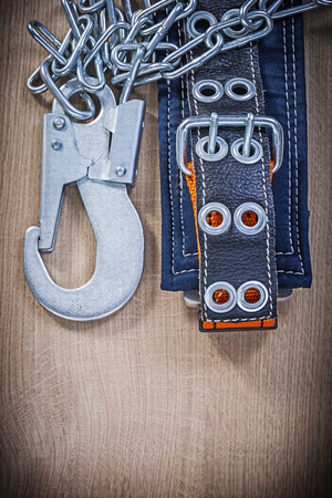 metal chain: Safety harness with metal chain on wooden board construction concept.