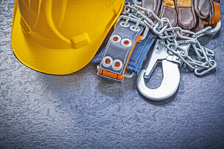building safety: Construction safety harness protective gloves building helmet on black background maintenance concept.