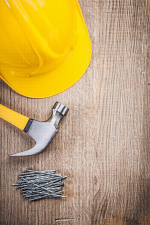 claw hammer: Claw hammer construction nails building helmet on wooden board.