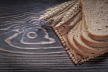 brown bread: Ripe rye wheat ears sliced brown bread wicker mat food and drink concept.