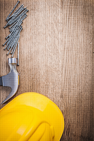 claw hammer: Claw hammer metal construction nails building helmet on wooden board.