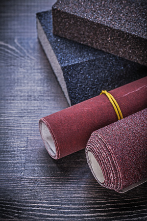 emery paper: Rolled emery paper sanding sponges on vintage wooden board abrasive materials. Stock Photo