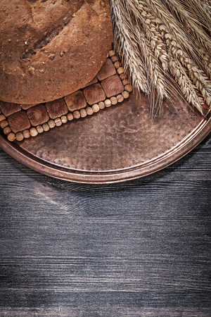 brown bread: Vintage copper tray with loaf of brown bread wheat rye ears on wood board. Stock Photo