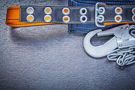 building safety: Construction body belt with metal chain on black background maintenance concept.