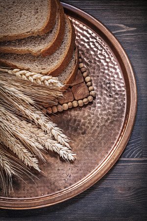Rye wheat ears sliced newly-baked bread vintage copper tray food and drink concept. Stock Photo