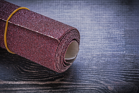 emery paper: Roll of sandpaper on vintage wooden board abrasive equipment. Stock Photo