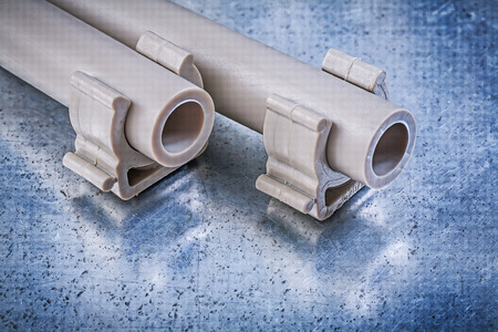 waterpipe: Plastic water-pipes pipe clamps on metallic background construction concept.