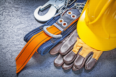 Construction safety harness protective gloves hard hat on black background maintenance concept.