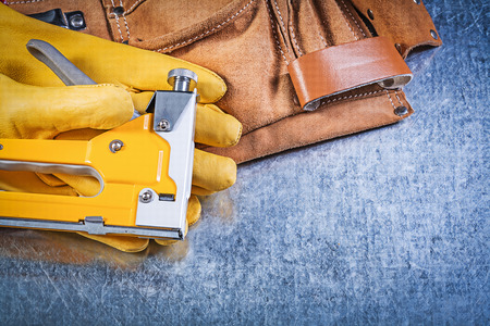 toolbelt: Collection of leather tool belt protective gloves construction stapler on metallic background. Stock Photo