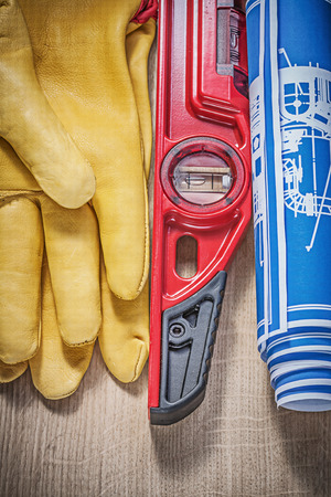 construction level: Protective leather gloves construction level blue blueprints on wooden board. Stock Photo