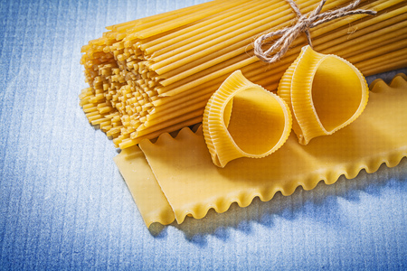 青色の背景の食べ物や飲み物のコンセプトにマカロニ製品の組成物。