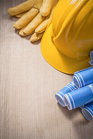 Blue construction plans hard hat leather protective gloves on wooden board.