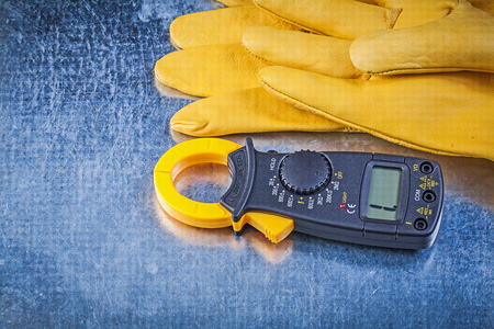 protective gloves: Digital clamp meter protective gloves on metallic background.