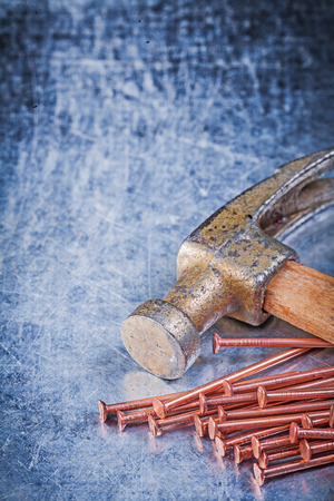 claw hammer: Claw hammer brass construction nails on metallic background.