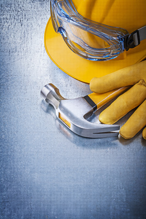 claw hammer: Safety glasses gloves building helmet claw hammer on metallic background. Stock Photo