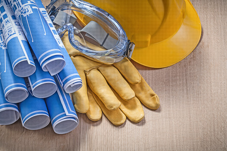 workwear: Safety workwear engineering drawings on wooden board construction concept. Stock Photo