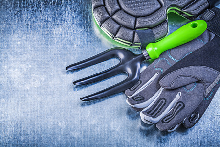 protectors: Gardening safety gloves knee protectors trowel fork on metallic background agriculture concept. Stock Photo