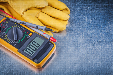 dielectric: Digital electrical tester test leads pair of safety gloves on metallic background.